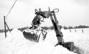 Bagger kämpft sich durch Schneeverwehungen auf Rügen